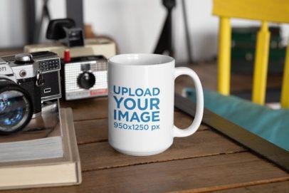 Mockup of a 15 oz Coffee Mug Placed Next to Some Vintage Cameras 33192