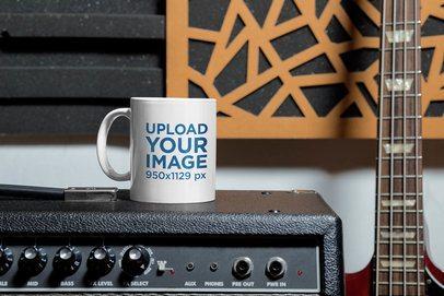 Mockup of an 11 oz Coffee Mug Placed Next to a Bass Guitar 33331