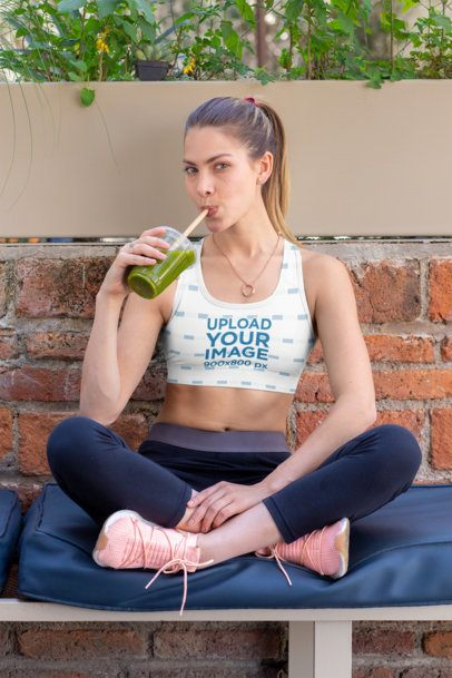 Mockup of a Woman Wearing a Sublimated Sports Bra and Drinking a Smoothie 32768