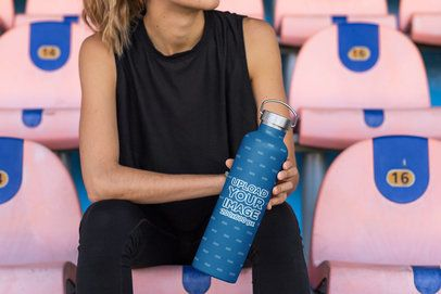 Mockup of a Woman Holding an Aluminum Bottle at a Stadium 33504