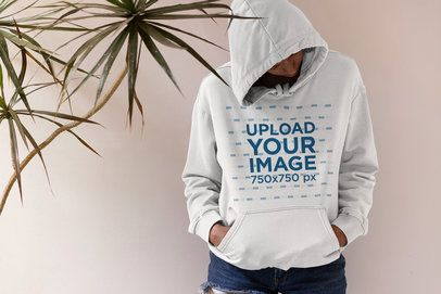 Hoodie Mockup of a Woman Standing Next to an Indoor Plant 33748