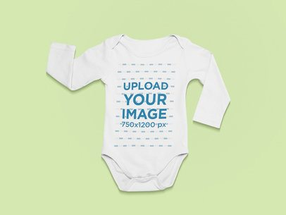 Front-View Mockup of a Long Sleeve Onesie Against a Flat Surface 25738