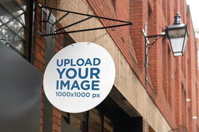 Mockup of a Circular Sign Hanging from a Store 4118-el1