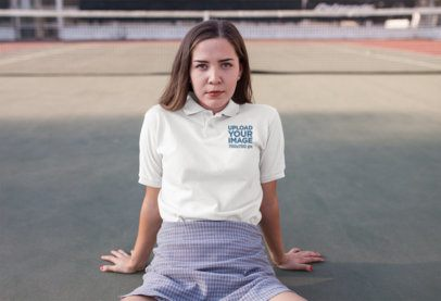 Mockup of a Woman Wearing a Polo Shirt Template While Sitting on a Tennis Court 15722a