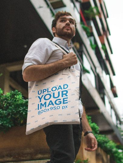 Tote Bag Mockup Featuring a Serious Man Walking Down the Street 17100a