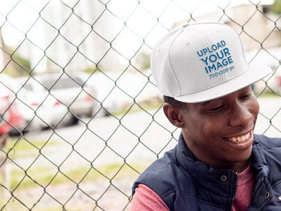 Snapback Hat Mockup of a Smiling Man Leaning on a Fence 11775a