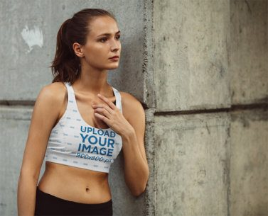 Sports Bra Mockup Featuring a Woman Leaning Against a Wall 37450-r-el2