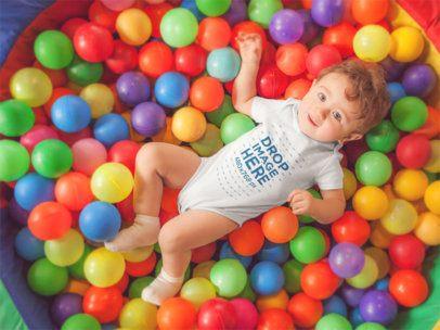 Pretty Baby Boy Having Fun at a Ball Pit Wearing a Onesie Mockup 14021