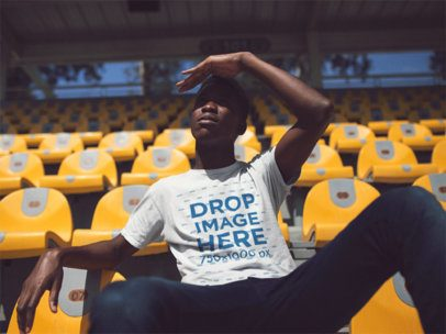 Mockup of a Black Dude Sitting in a Stadium Taking a Look at the Place While Wearing a T-Shirt a14252