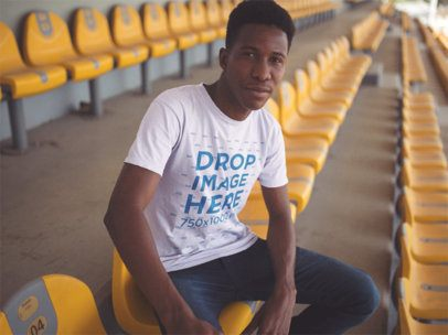 Young Man Wearing a Round Neck Short Sleeved Tshirt While Sitting in a Stadium Mockup a14250