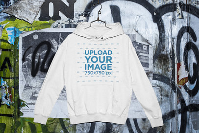 Mockup of a Pullover Hoodie Placed on a Hanger by a Graffiti Wall m427