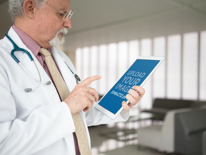 Mockup Featuring a Senior Doctor Using an iPad Pro in Portrait Position  12436a