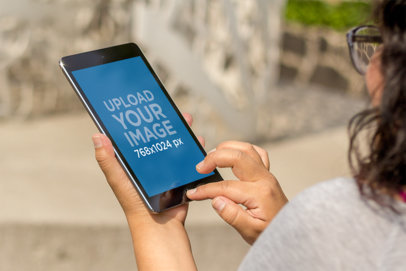 Mockup of a Woman with Glasses Using an iPad Mini 4130a