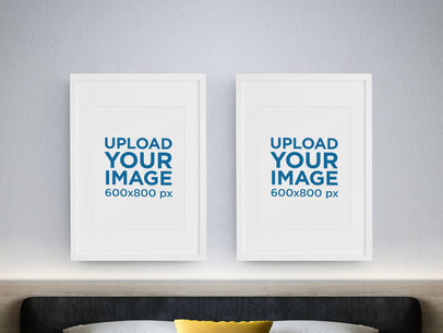 Mockup of Two Vertical Art Prints Hanging on a Bedroom's Wall m972