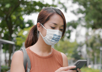 Face Mask Mockup of a Woman Checking Her Mobile Phone at a Park 46963-r-el2