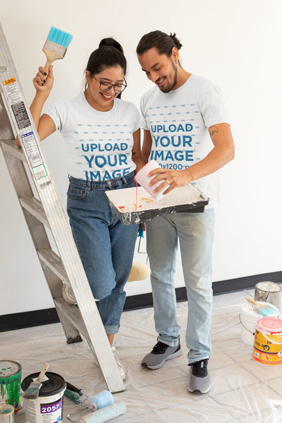 T-Shirt Mockup of a Happy Young Couple Painting Their Apartment m1084