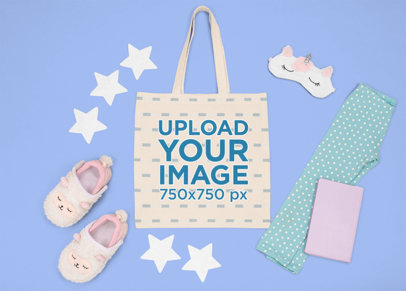 Mockup of a Flat Laid Tote Bag Featuring a Kid's Sleeping Outfit m1270
