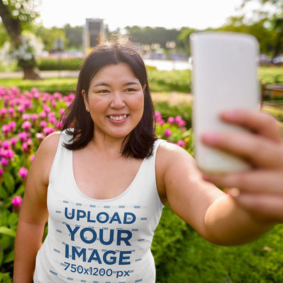 Tank Top Mockup Featuring a Smiling Woman Taking a Selfie at a Garden m2107-r-el2