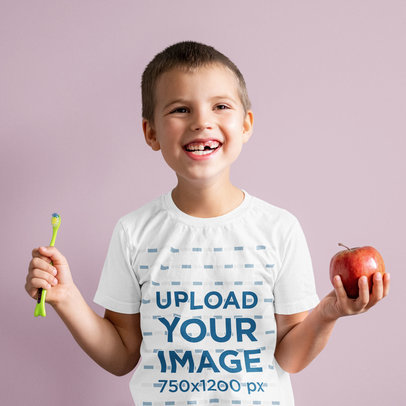 T-Shirt Mockup Featuring a Happy Kid Holding an Apple and a Toothbrush m1574-r-el2