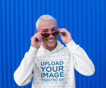 Hoodie Mockup Featuring a Happy Young Man Posing Against a Blue Wall m1972-r-el2