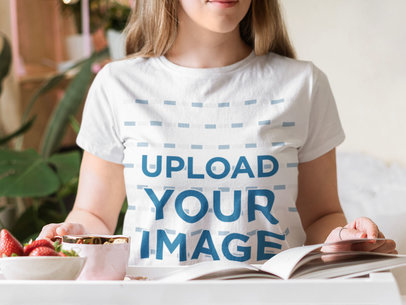 T-Shirt Mockup of a Young Woman Reading While Having Breakfast m1606-r-el2