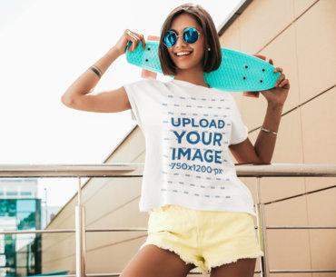 T-Shirt Mockup of a Joyful Young Woman Holding a Small Skateboard m2463-r-el2