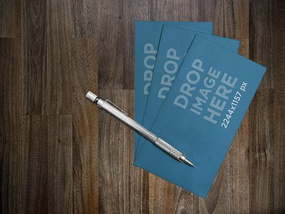Mockup of a Set of Business Cards Lying Next to a Pen on a Desk a6257