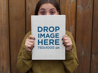 Woman Holding a Book Cover Mockup With Her Eyes Wide Open a12032