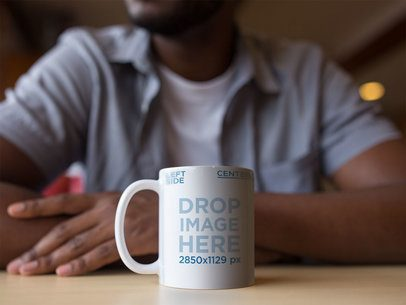 11 oz Coffee Mug Mockup Featuring a Man Sitting at a Table 12324a