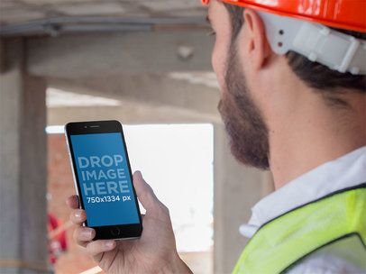 Mockup of a Worker Looking at His iPhone in Portrait Mode 12424