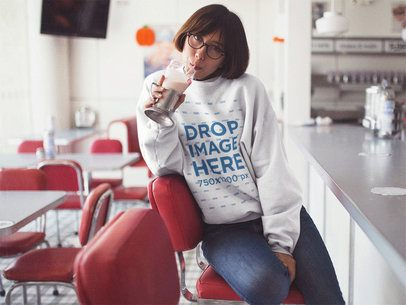 Crewneck Mockup of a Cool Girl with Short Hair and Glasses Drinking a Milkshake at a Diner a12665