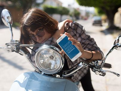 iPhone 6 Mockup of a Woman Riding a Blue Scooter a12397