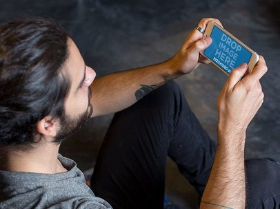 iPhone 6 Plus Mockup in Landscape View of a Young Man Playing at his Apartment a13111