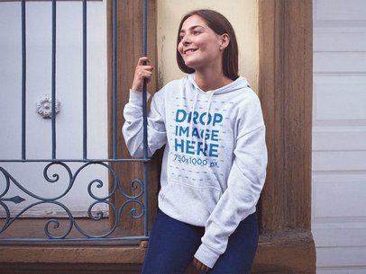 Smiling Pretty Girl Wearing a Pullover Hoodie Mockup Sitting on a Small Ledge a12722