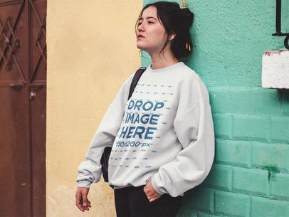 Crewneck Mockup of a Young Woman Leaning Against a Green Wall in the Street a12683